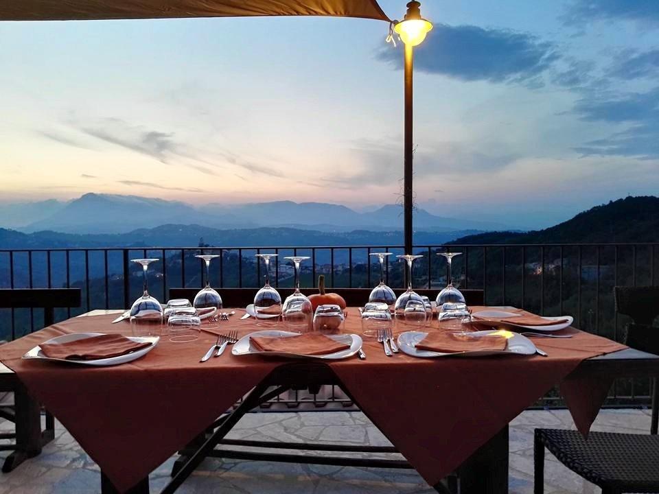 Tavola pronta per la cena nella terrazza con il tramonto nelle montagne