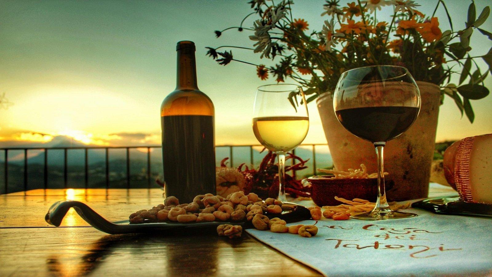 Nella tavola della terrazza di fronte al tramonto ci sono due bicchieri di vino,una bottiglia, formaggio e snack