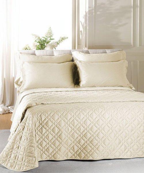 Una camera da letto arredata in color bianco, copriletto e federe dei cuscini di color crema e la testata imbottito