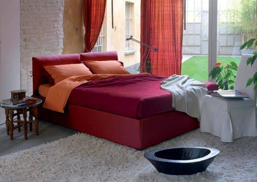 Un letto di color rosso con copriletto, cuscini di color bordeaux e arancione e davanti una poltrona bianca. Vista da dietro le finestre di un prato grande