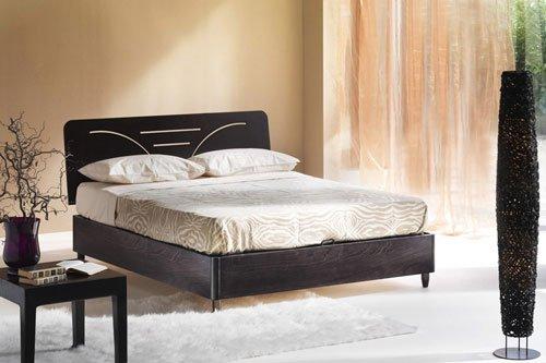 Un letto di color nero con copriletto e cuscini di color crema, una lampada da terra di color nero e un tavolino con vaso di color viola
