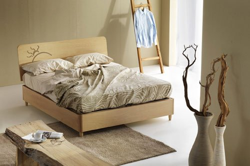 Una stanza con letto grigio con copriletto e cuscini di color crema, una scaletta di legno con una camicia appesa e vasi di color bianco con dentro dei rami secchi