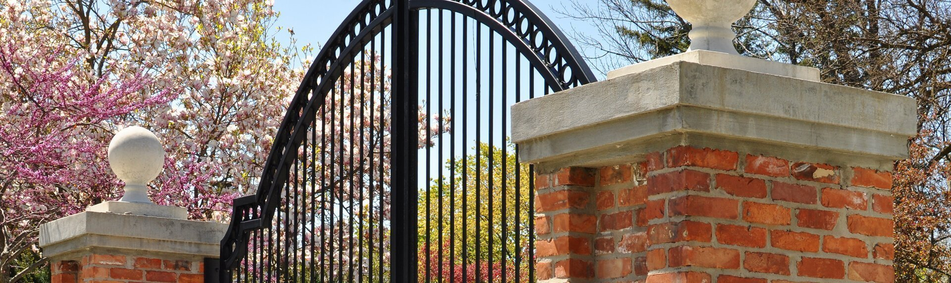 tope of curved metal gate and brick pillars
