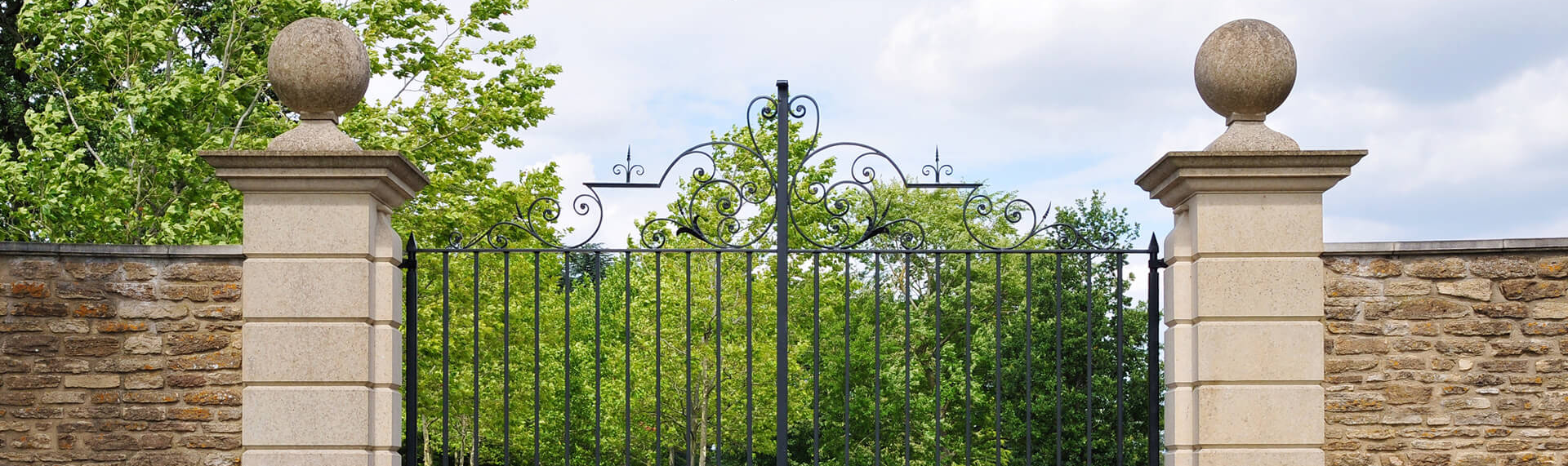 view of upper half of metal gates and stone pillars