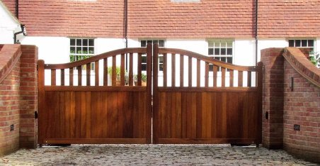 Wooden Gates, Iroko Hardwood, Convex toprail, stright mid rail, half boarded, brick piers and walls. GSM intercom and FAAC 770 underground motors. Induction loop egress control, induction loop. Portcullis electric Gates LTD.