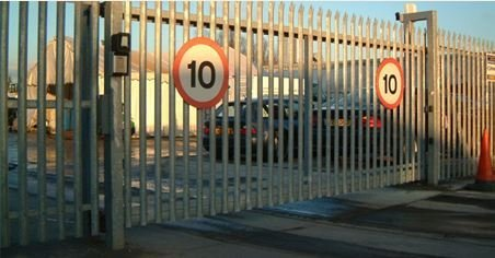 large metal security gates with speed limit signs