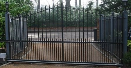 curved black gates with trees in background