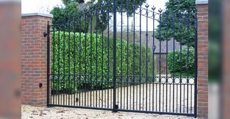 tall black gates with hedge rows either side
