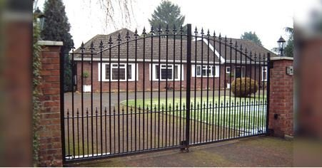 large double metal gates infront of small house