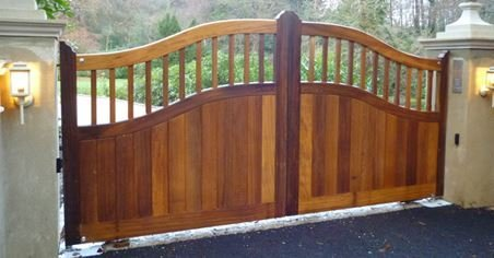 Wooden Gate, Curved top and midrail, half boarded, White piers and white walls, tarmac driveway, drive way lights. Portcullis electric Gates LTD.
