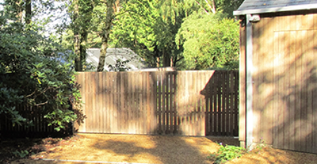 flat top wooden gate with green trees behind