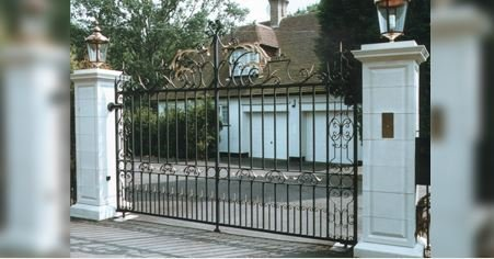 metal gates with white pillars either side