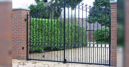 tall and curved black gates with large hedgerow to the left