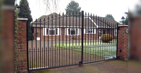 wide double metal gates infront of small house