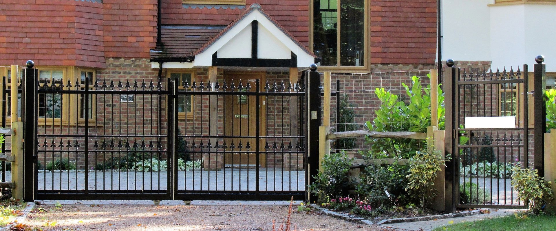 detailed black metal gate infront of brick house