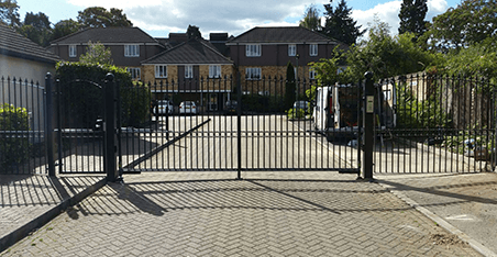 wide metal gates and fence infront of large courtyard and home