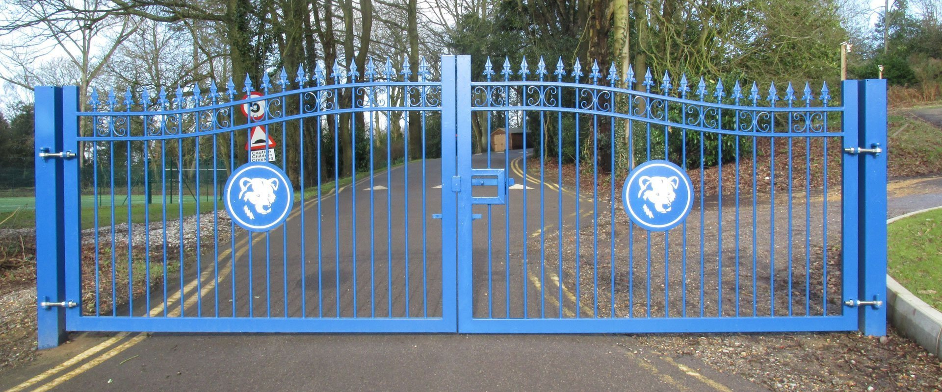 blue double metal gates infront of driveway