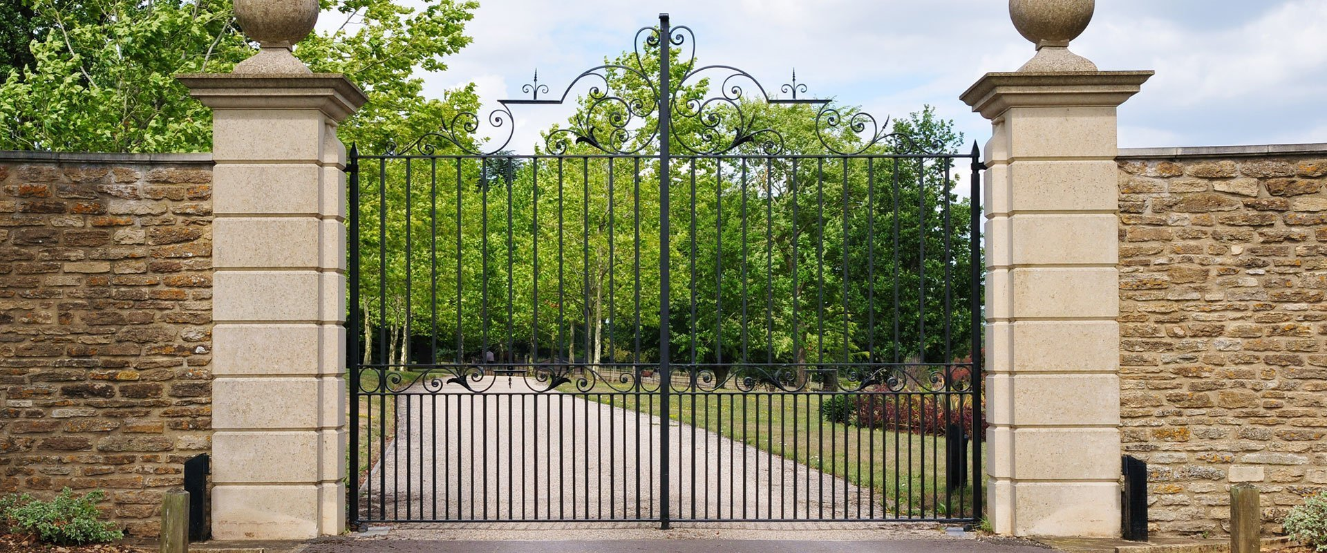 ornate detailed black metal gates with tall sandstone pillars