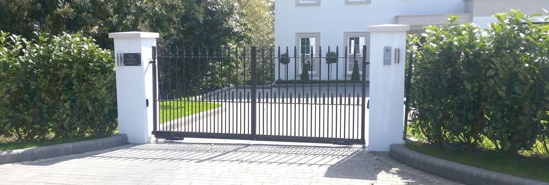double metal gates in front of a large white house with gravel drive