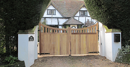 Wooden Gate, white piers and wall, Yew Bush hedging, concave toprail, straight midrail, manual gate. Iroko hardwood. Portcullis Electric Gates LTD.