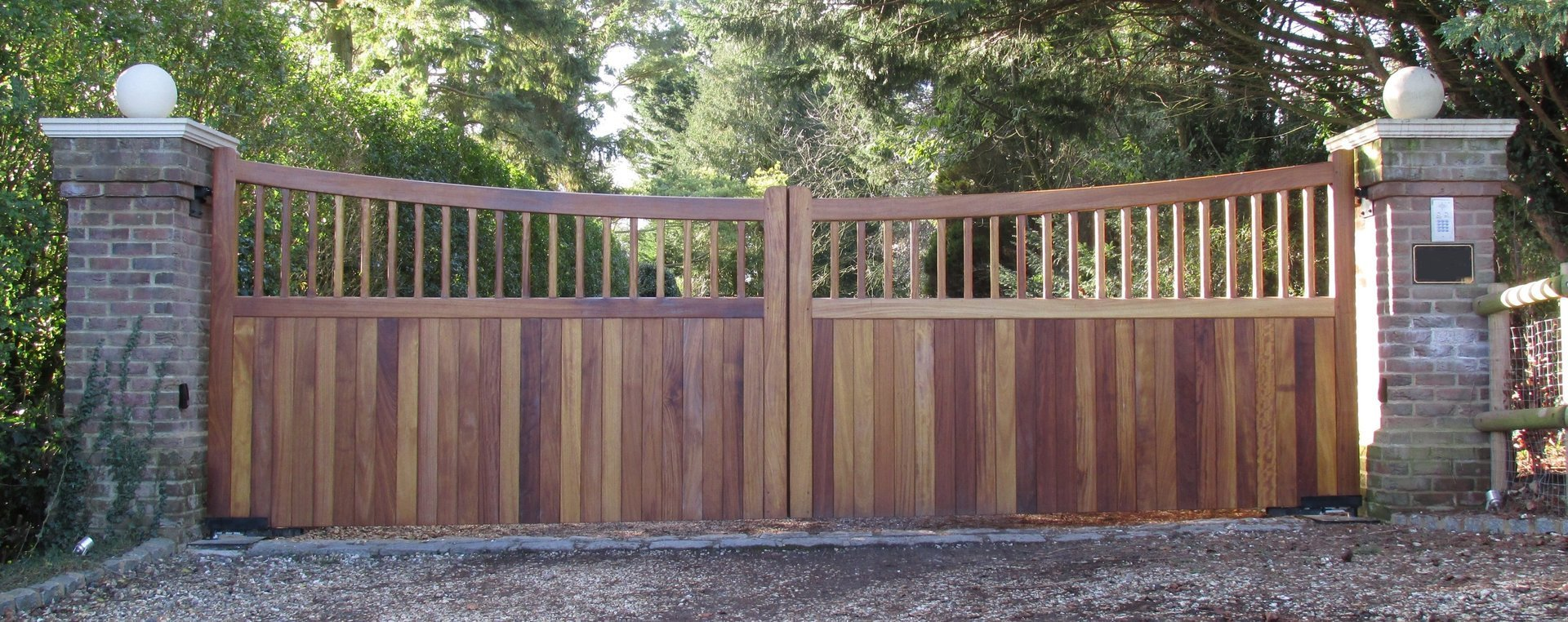 wide wooden gate with brick pillars