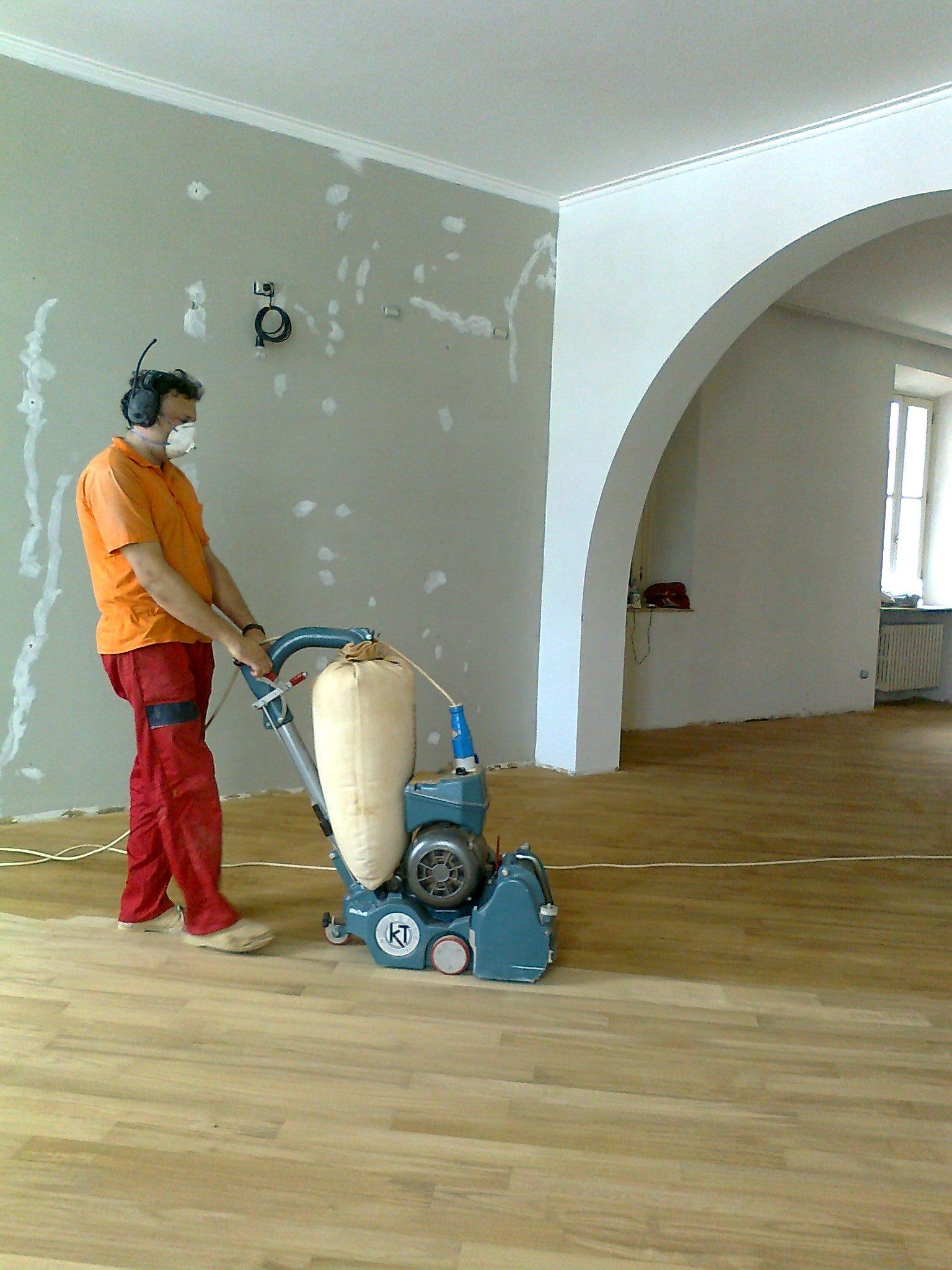 operaio con macchinario per lamatura mentre lavora sul pavimento di una casa