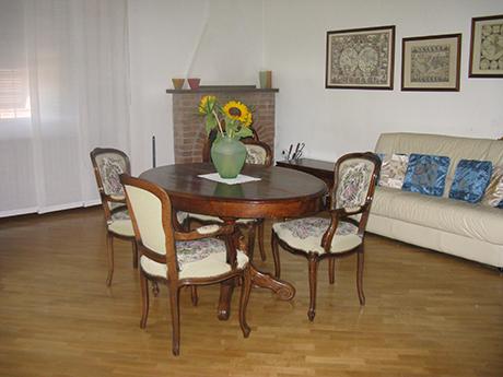 sala da pranzo con vaso di fiori sul tavolo in legno con sedie, divano, cuscini e tenda bianca