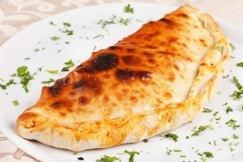 Calzone ripieno con pomodoro, mozzarella e prosciutto.