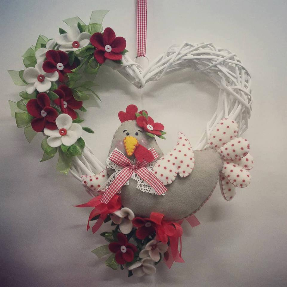 Un cuore di paglia con una gallina e dei fiori bianchi e rossi