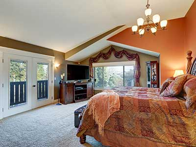 Elegant Master suite with vaulted ceiling, red and taupe walls, gorgeous wood carved queen bed facing media cabinet with flatscreen TV and glass doors to view deck. Northwest, USA