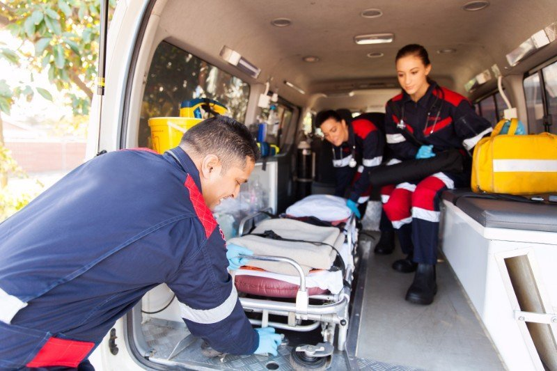 paramedici estraggono lettino dall'ambulanza