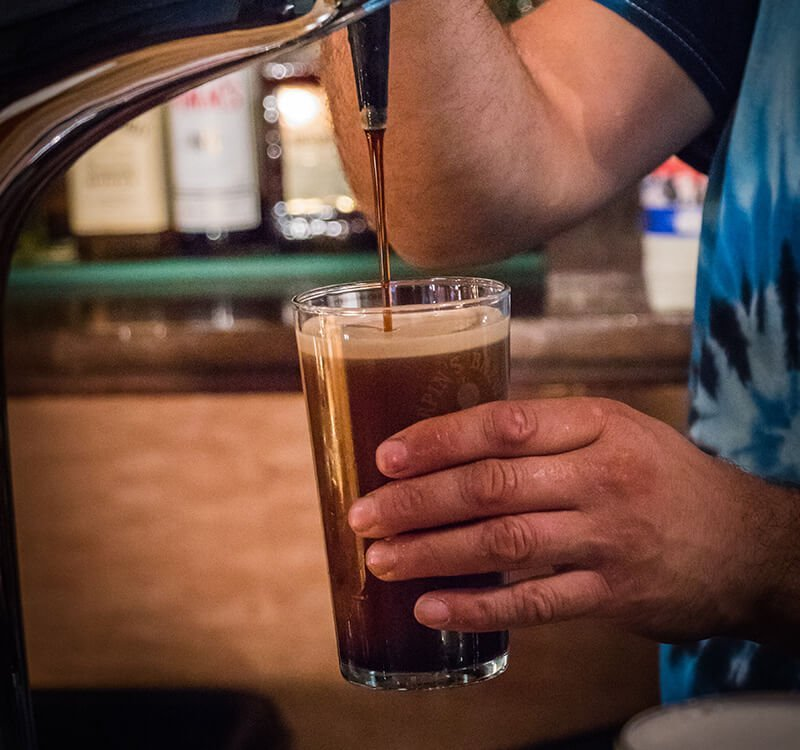 dark ale being poured into a pint