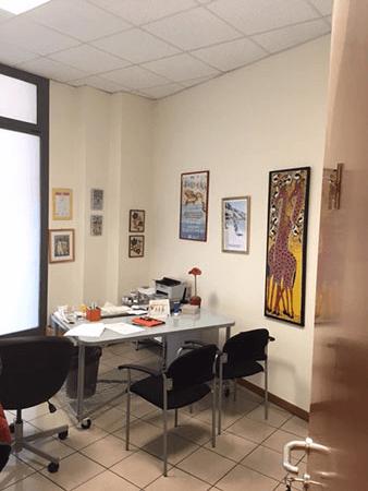 una scrivania in vetro e delle sedie in un ufficio