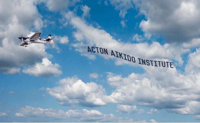 Photo od airplane with Aikido banner attached advertising Aikido lessons at Martin Acton's Aikido Institute.