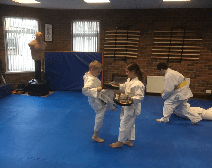 Children kneeing pads practicing aikido