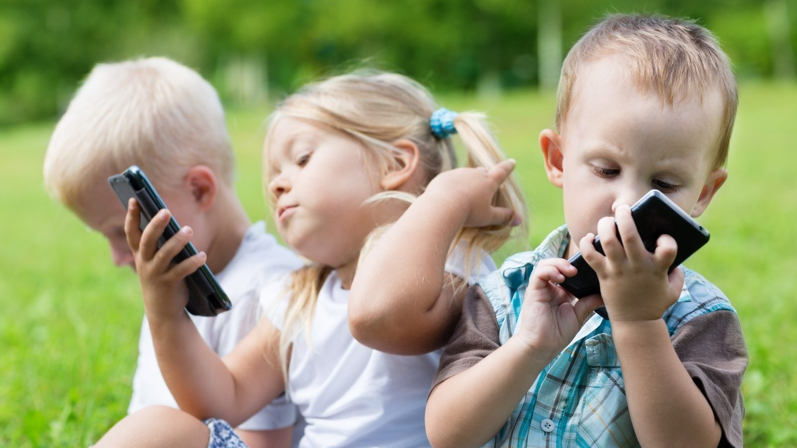 This is a photo of three very young children outdoors playing with smartphones.