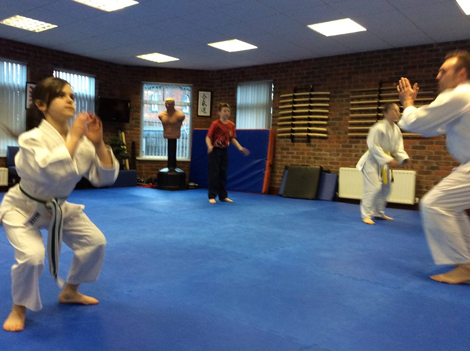 Aikido children's class doing squats to strengthen the legs. Martin Acton's Aikido Institute