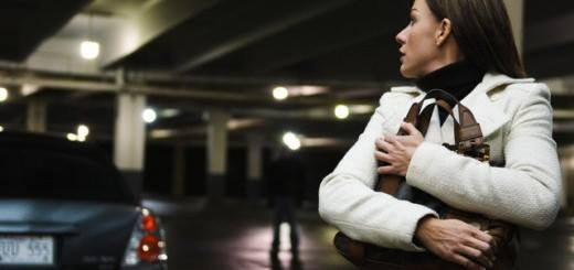 A lady alone in a dark car park and a dark image in the shadows behind hers
