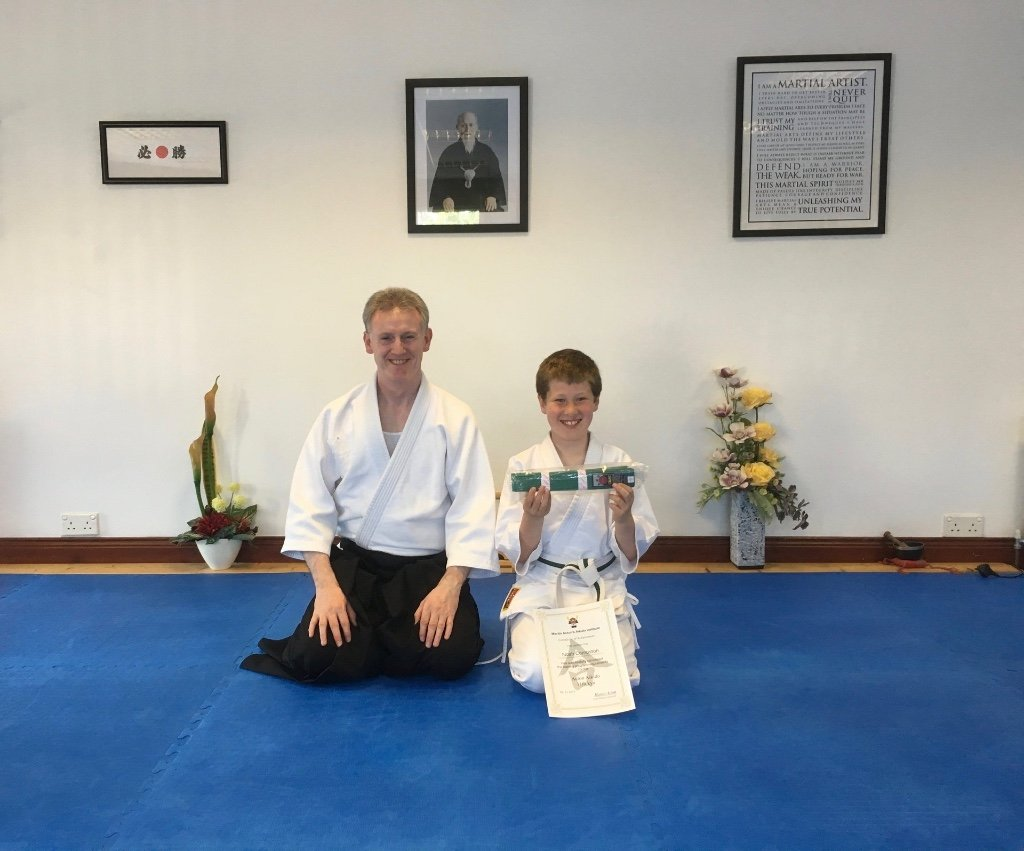 Aikido child getting his green belt with Martin Acton sensei. Martin Acton's Aikido Institute