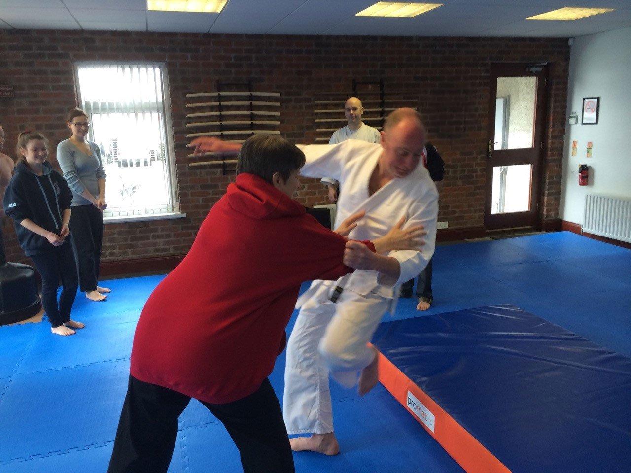 Self defense class. Elderly woman trowing attacker on crash mat. Martin Acton's Aikido Institute.