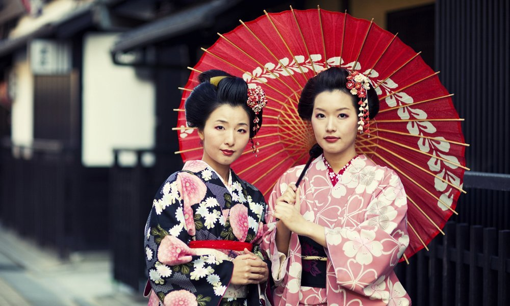 Two Japanese women in traditional clothing holding an umbrella .