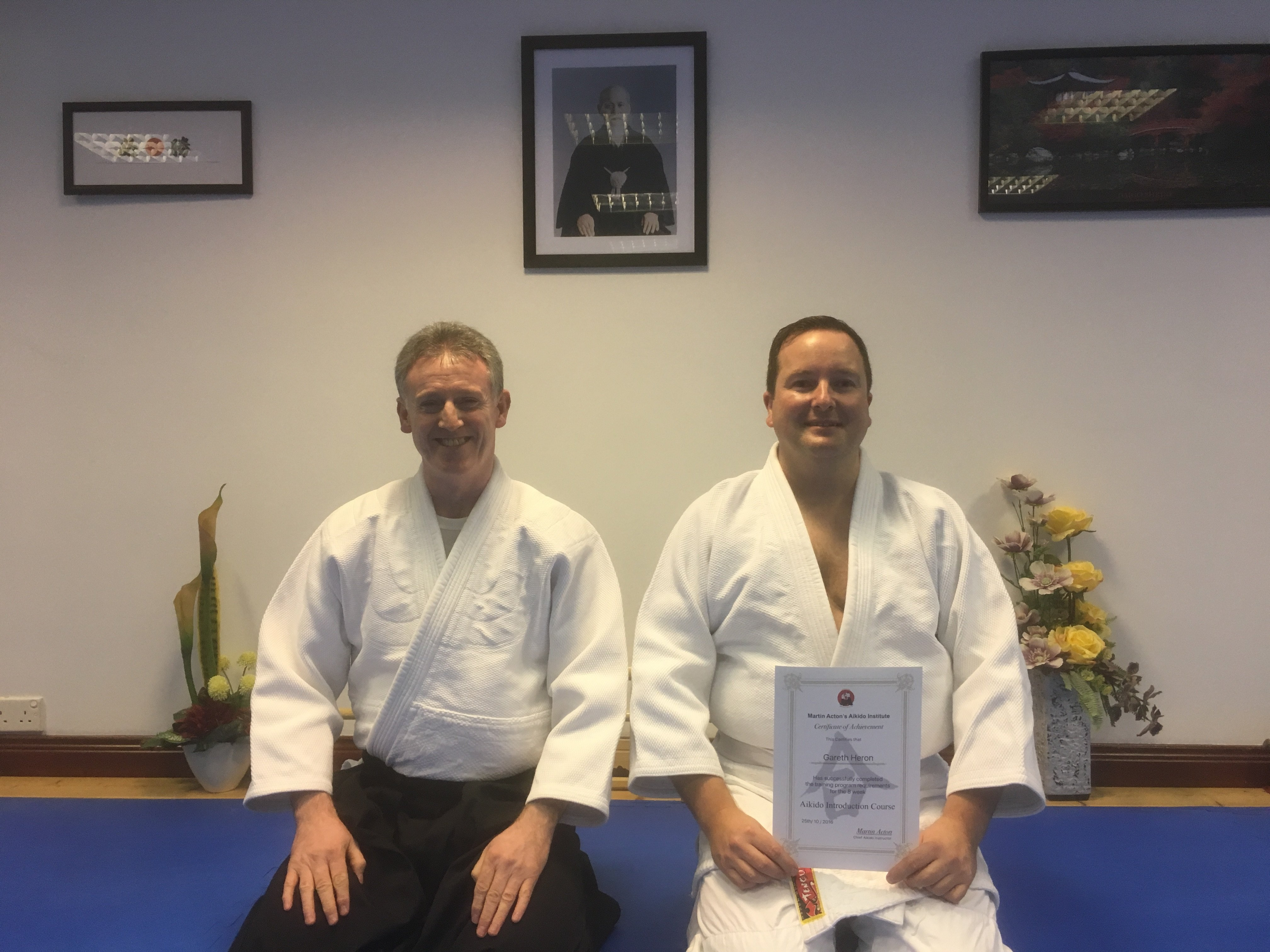 Teacher and student with certificate kneeling