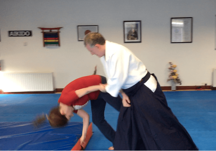Aikido 8-Week Introduction Course. There is a  photo of a lady learning to fall safely on a crash mat.   Martin Acton's Aikido Institute