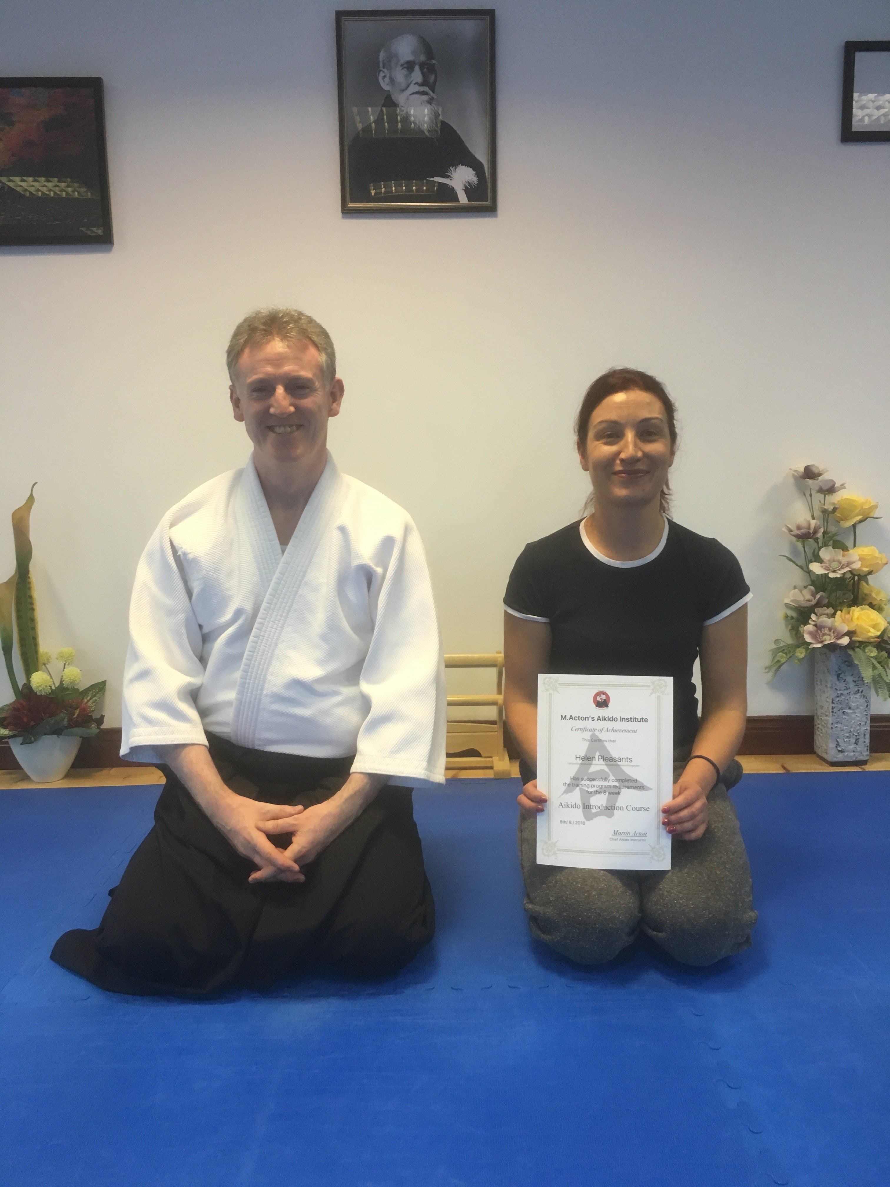 Teach and student with certificate kneeling