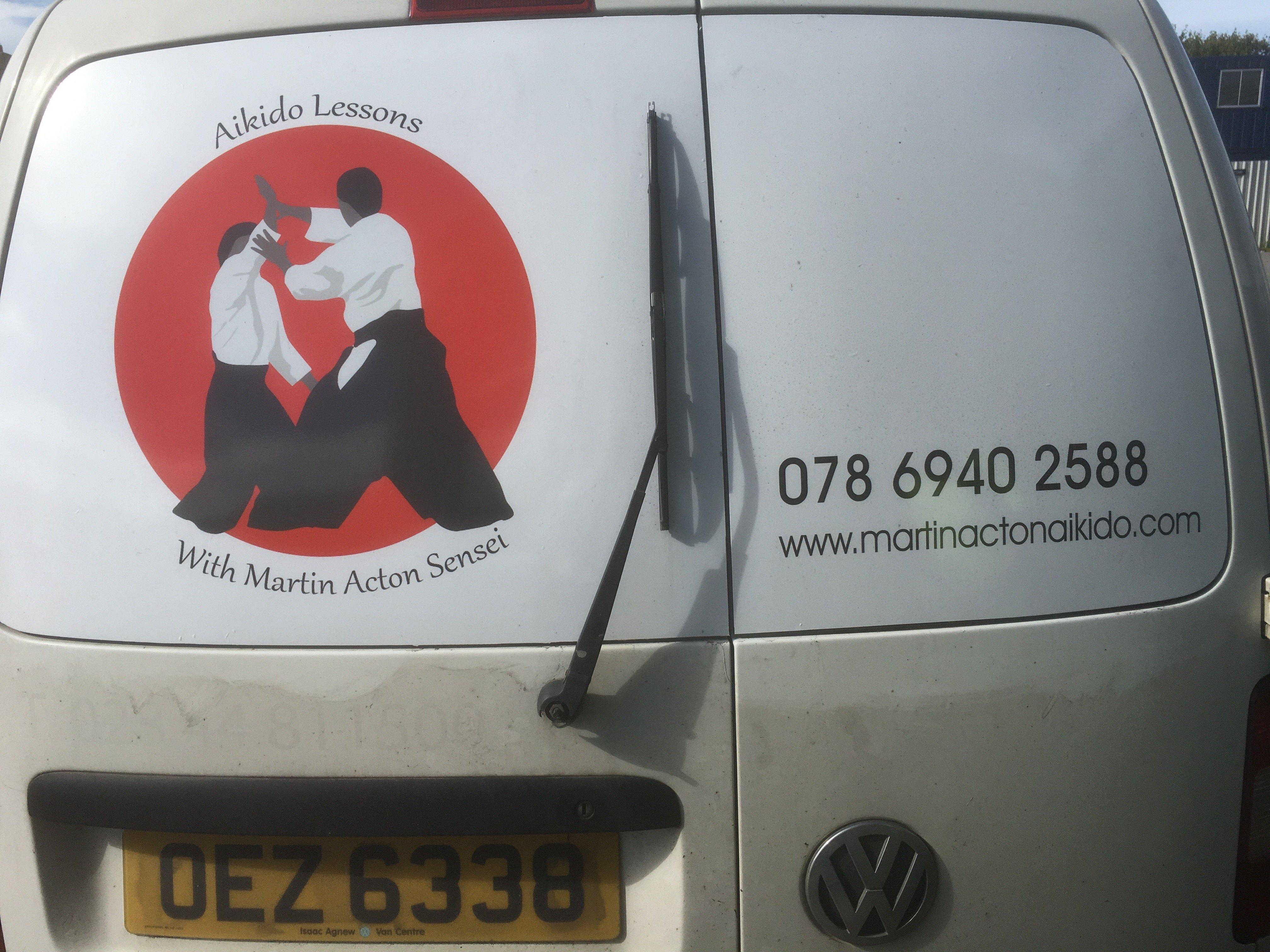 Back of a white van with Martin Acton Aikido Institute's logo