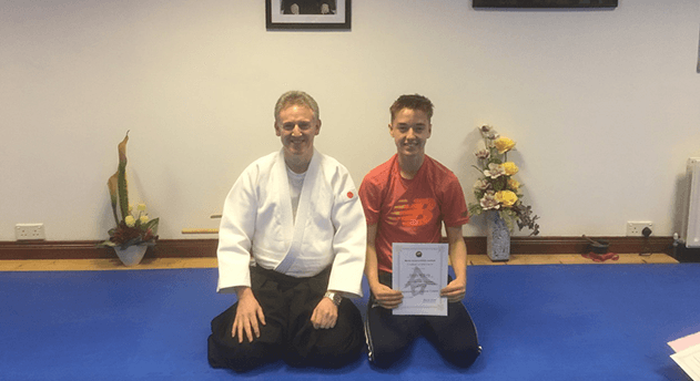 learning to speak Japanese. You boy receives his certificate for graduating 6 week course. Martin Acton's Aikido Institute.