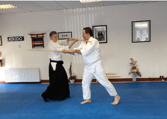 Bokken course. Martin acton sensei and Marian performing a move with wooden Japanese sword. Martin Acton's Aikido Institute