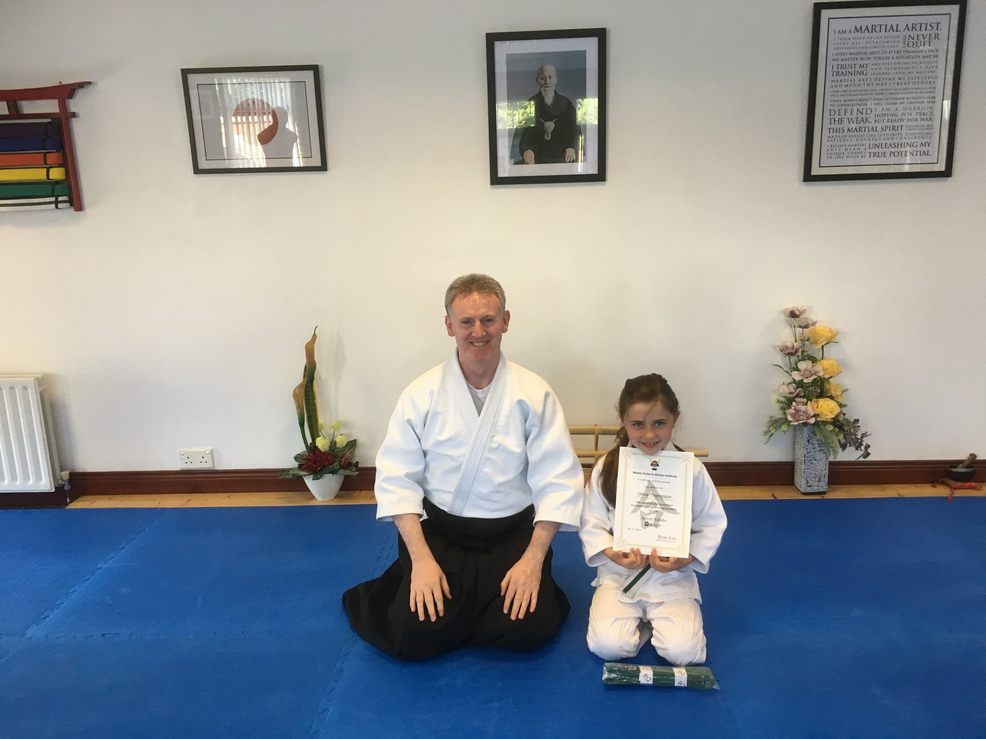 Olivia Thompson receiving her 10th kyu certification with Martin Acton sensei