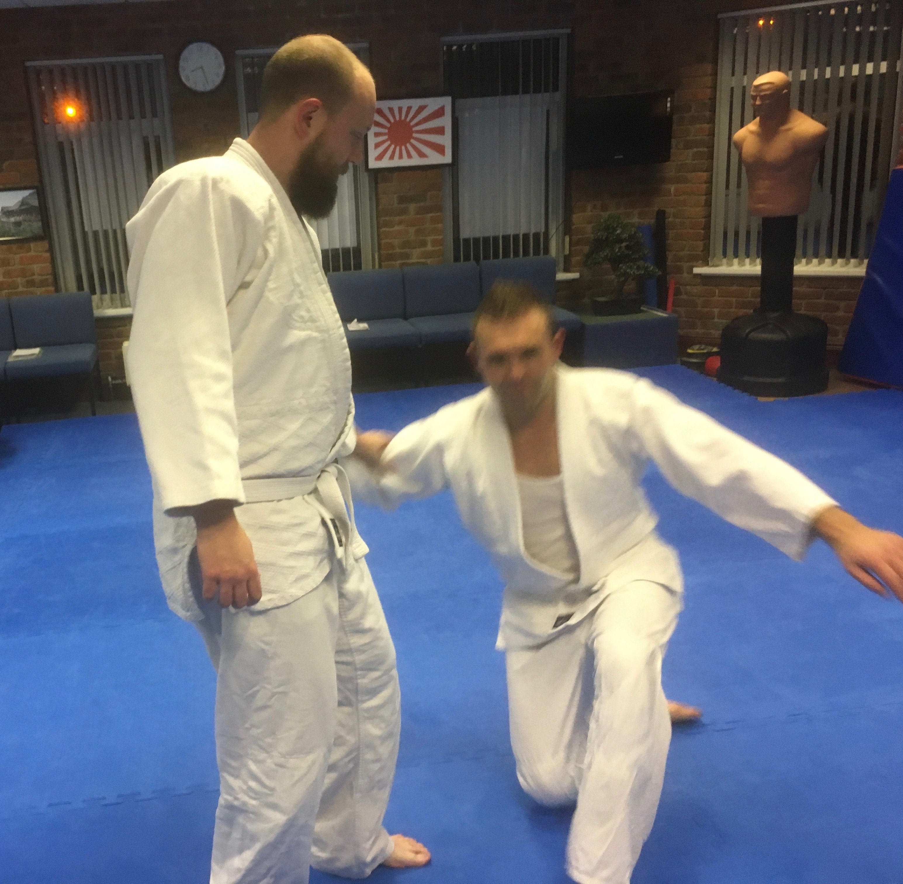 A photo showing how easy it is to put a person down by taking his balance. Martin Acton's Aikido Institute