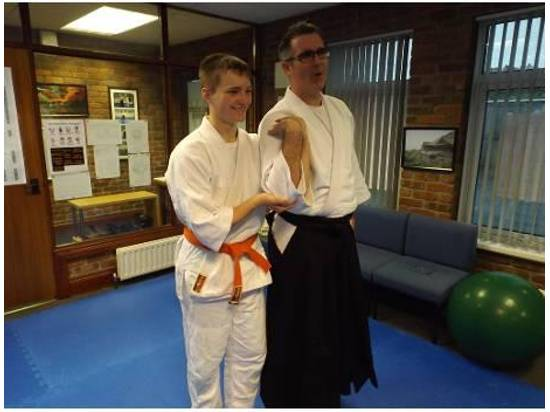 Aikido boy learning to restrain an older man. Martin Acton's Aikido Institute